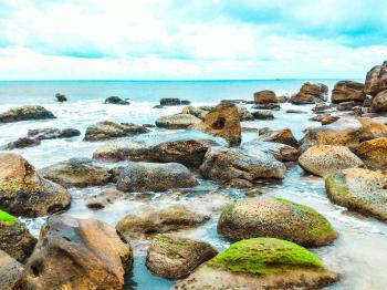 Landscape Photography of Rocks With Moss Surrounded by Body of Water