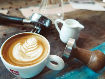 Latte on Cup Beside Milk Cup