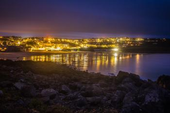 Lighted City in Distance Near Body of Water