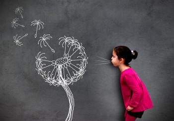 Little cute girl blowing dandelion seeds on chalkboard