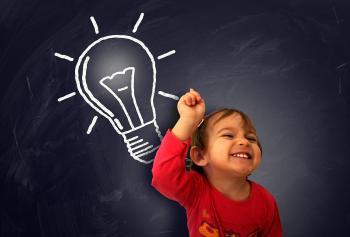 Little cute girl having a good idea on the blackboard