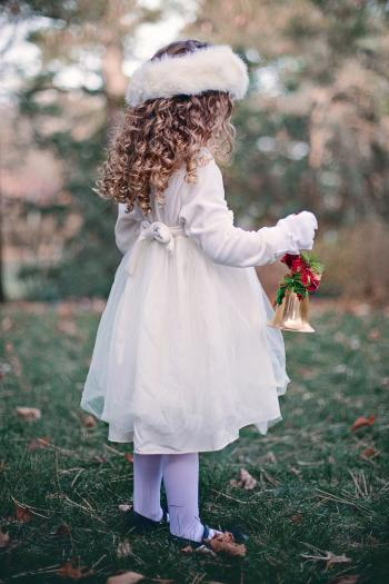 Little Girl Holding a Christmas Bell