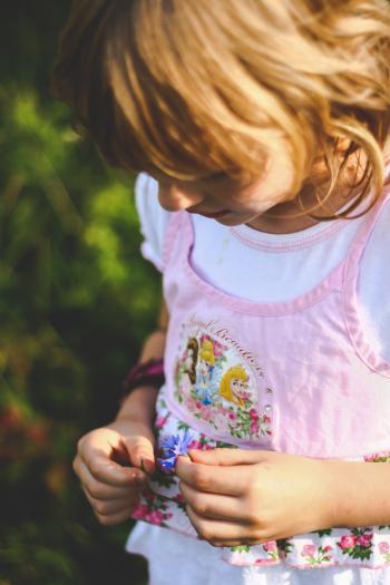 Little girl looks on flower