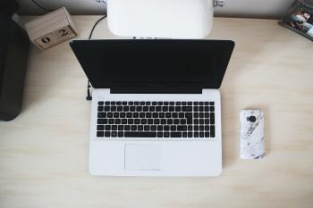 Macbook Beside Smartphone on Desk