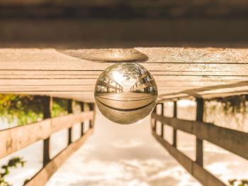 Macro Photography of Round Glass Ball on Top of Brown Wooden Dock