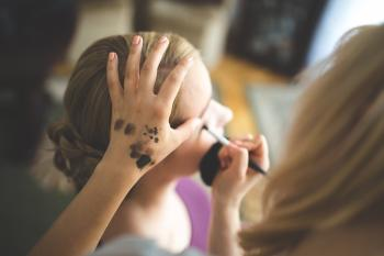 Make up artist applying shadow to a woman