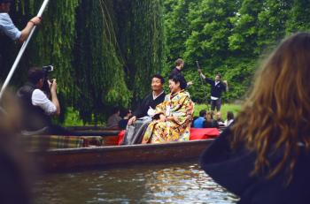Man and Woman Sitting on Brown Canoe