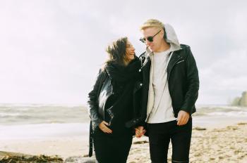 Man and Woman Wearing Jackets Near Seaside Under Cloudy Sky