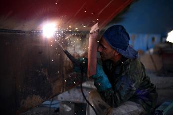 Man Holding Welding Rod and Welding Mask While Working