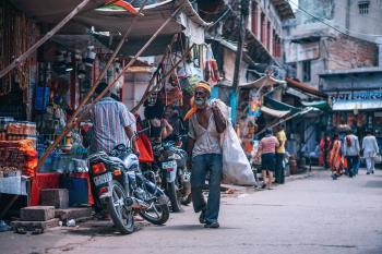 Man Holding White Sack Walking Beside Street Stores