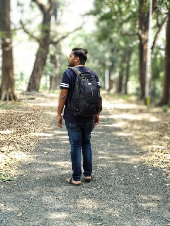 Man in Black and White T-shirt and Blue Denim Jeans Carrying Backpack