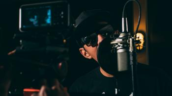 Man in Black Cap and Black Framed Sunglasses in Front Recording Microphone