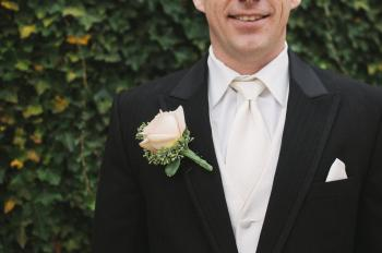Man in Black Formal Suit With White Necktie Beside Green Bush in Shallow Focus Photography