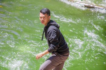 Man in Black Hoodie Standing in Front of Body of Water