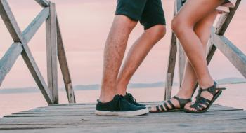 Man in Black Low-top Sneakers Leaning Towards Woman in Black Gladiator Flat Sandals on Dock