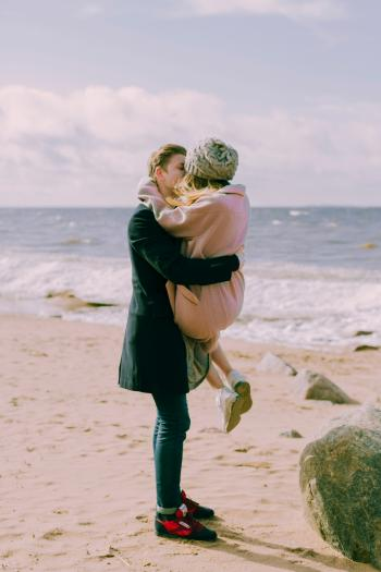 Man in Black Overcoat and Blue Denim Jeans Kissing While Carrying a Woman in Pink Overcoat and Knit Cap on Shore at Daytime