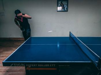 Man in Black Shirt Standing Near Blue Wooden Pingpong Table