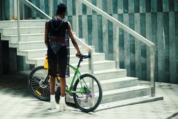 Man in Black Sleeveless Shirt Holding Green Mountain Bike Near Metal Staircase