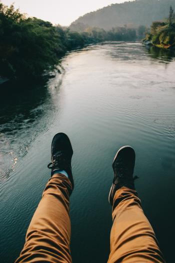 Man in Black Sneakers And Brown Pants Sitting in Front of the River