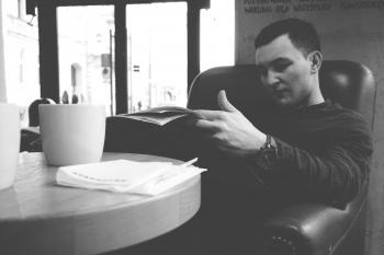 Man in Black Sweater Reading Newspaper