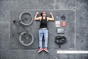 Man in Black Tank Top Laying on Gray Concrete Surface Near Black Bike