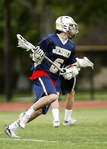 Man in Blue and White Jersey Playing Lacrosse