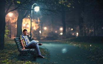 Man in Blue Denim Jeans Sitting Down by Wooden Bench Near Post Lamp Lighted