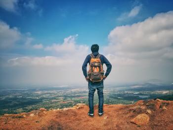 Man in Blue Dress Shirt and Blue Jeans and Orange Backpack Standing on Mountain Cliff Looking at Town Under Blue Sky and White Clouds
