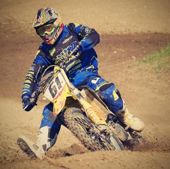 Man in Blue Motorcycle Suit Riding on Yellow Dirt Motorcycle during Daytime