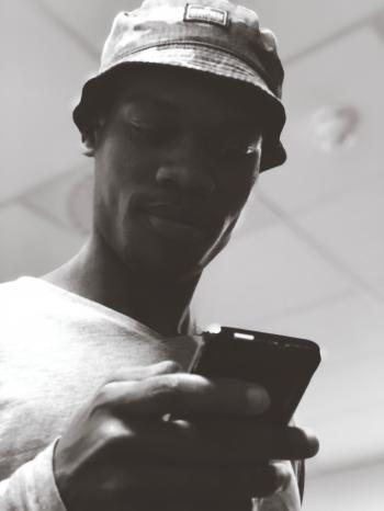 Man in Bucket Hat Holding Black Smartphone