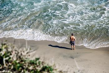 Man in Gray Shorts Standing on White Sand Beach during Daytime
