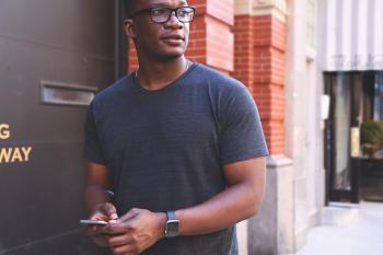 Man in Gray T-shirt Near Black Metal Wall