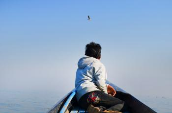 Man in Grey Hoodie and Black Pants Sitting in the Middle of Boat Looking at Bird in the Sky