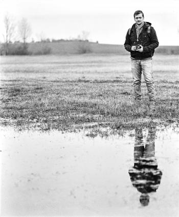 Man in Jacket Standing Near Body of Water Holding Camera in Grayscale Photography