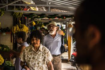 Man in Purple Polo Shirt and Brown Hat Behind Woman in Brown and White Floral Button-up T-shirt