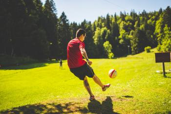 Man in Red T Shirt Playing Soccer during Daytime