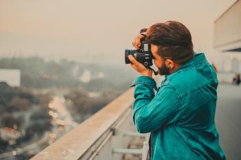 Man In Teal Button-Up Long Sleeved Shirt Shooting Using DSLR Camera