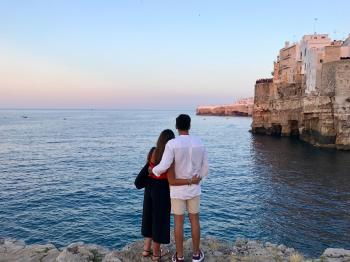 Man in White Dress Shirt Standing Beside the Woman in Black and Red Dress While Watching the Blue Calm Water Near Brown Concrete Buildings Under White and Blue Sky at Daytime