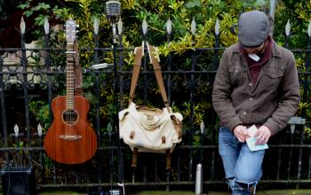 Man Leaning Against Black Steel Fence Beside White and Brown Sling Bag and Brown Acoustic Guitar