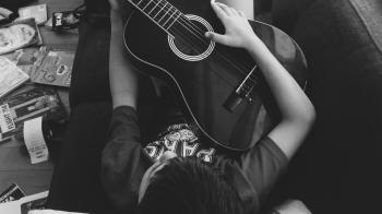 Man Playing Guitar Lying on Couch in Grayscale Photography