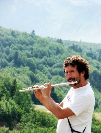 Man playing the flute in the mountains