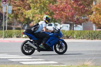 Man riding blue Kawasaki Ninja 250R in road