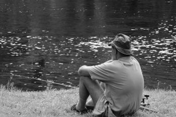 Man Sitting Facing Body Of Water