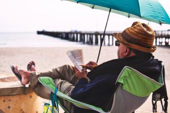 Man Sitting on Chair Under Blue Umbrella Near Beach