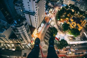 Man Sitting on High Rise Building Taking Photo Below