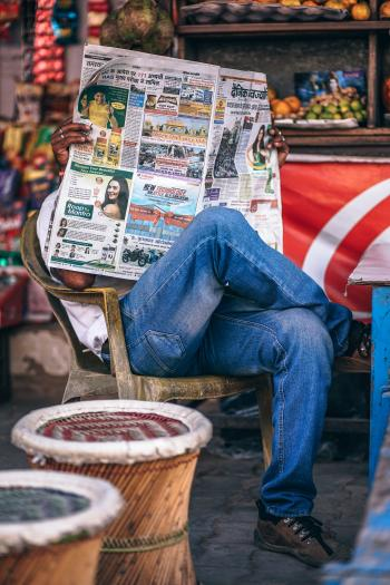 Man Sitting on Plastic Armchair Reading Newspaper