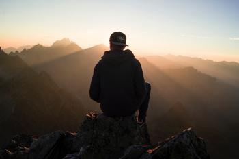 Man Sitting on the Mountain Edge