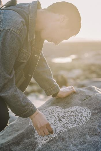 Man Sketching Heart on a Gray Rock