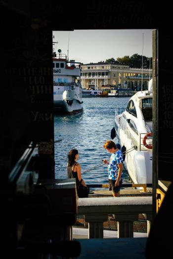Man Standing Beside Woman Near White Yacht