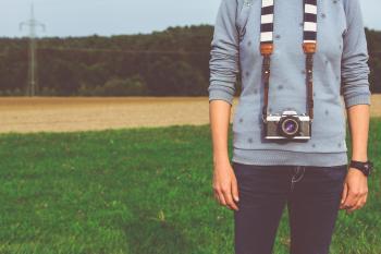 Man Standing Carrying Dslr Camera during Daytime